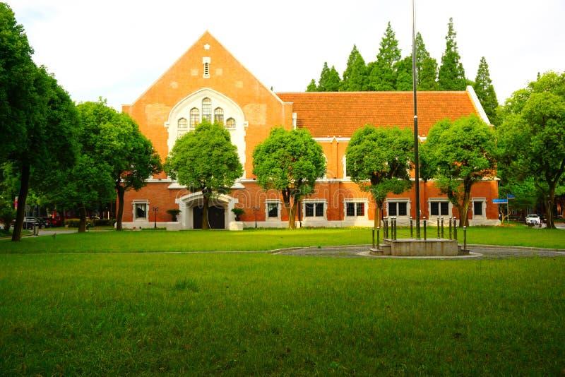 Πορτοκαλί σπίτι ύφους τούβλου ευρωπαϊκό πίσω από έναν πράσινο χορτοτάπητα στοκ φωτογραφία