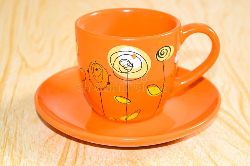 Πορτοκαλί φλυτζάνι σε ένα πιατάκι στοκ φωτογραφίες με δικαίωμα ελεύθερης χρήσης
