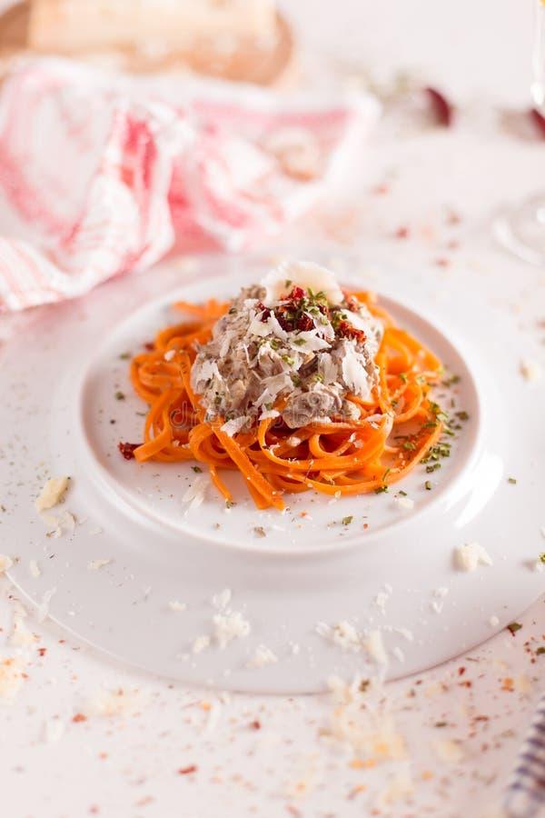 Πορτοκαλιά ζυμαρικά και άσπρη σάλτσα που εξυπηρετούνται στο άσπρο πιάτο στοκ φωτογραφίες