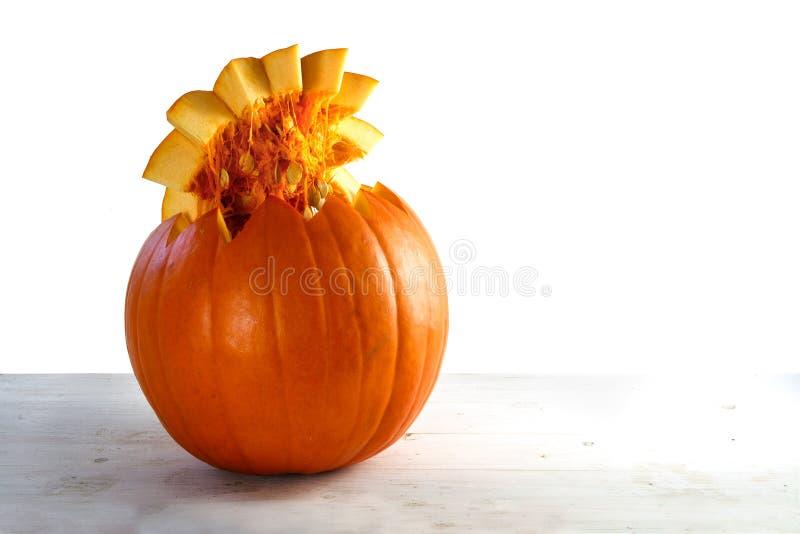 Πορτοκαλιά κολοκύθα που κόβεται ανοικτή με τους σπόρους στο καπάκι στο ανοικτό γκρι ξύλο στοκ φωτογραφία με δικαίωμα ελεύθερης χρήσης