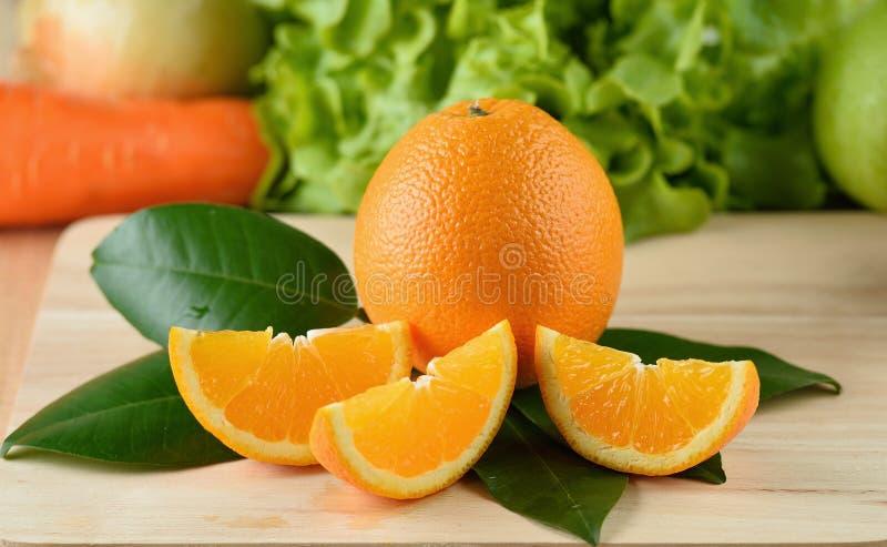 Πορτοκαλιά φέτα που απομονώνεται σε ένα ξύλινο υπόβαθρο στοκ φωτογραφίες