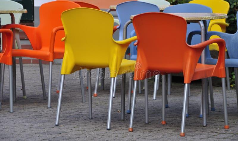 Πορτοκαλιές και κίτρινες πλαστικές καρέκλες στοκ εικόνες