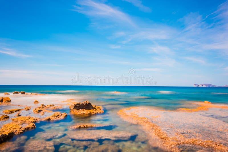 Πορτοκαλιοί βράχοι και μπλε θάλασσα στην ακτή Alghero στοκ εικόνες