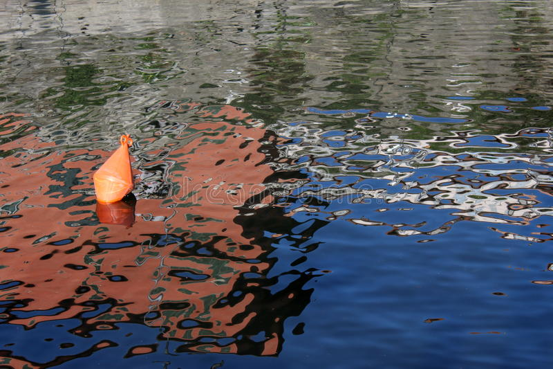 Πορτοκαλιοί πλαστικοί σημαντήρας και σπίτια που απεικονίζουν στο νερό στοκ φωτογραφία με δικαίωμα ελεύθερης χρήσης
