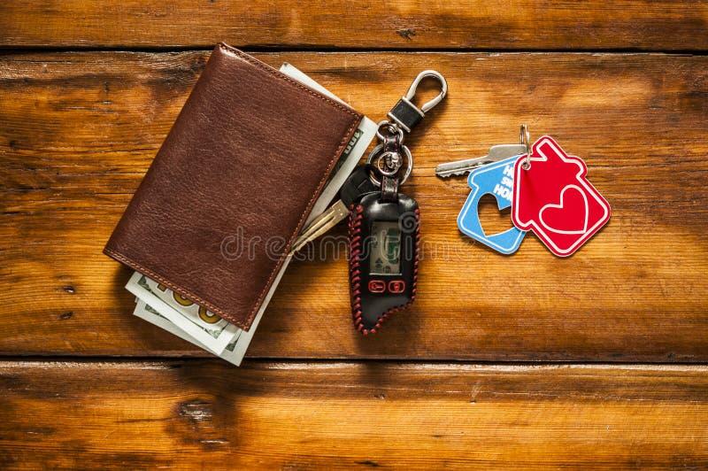 πορτοφόλι δέρματος και κλειδί αυτοκινήτων στον ξύλινο πίνακα με τους λογαριασμούς δολαρίων στοκ φωτογραφίες με δικαίωμα ελεύθερης χρήσης