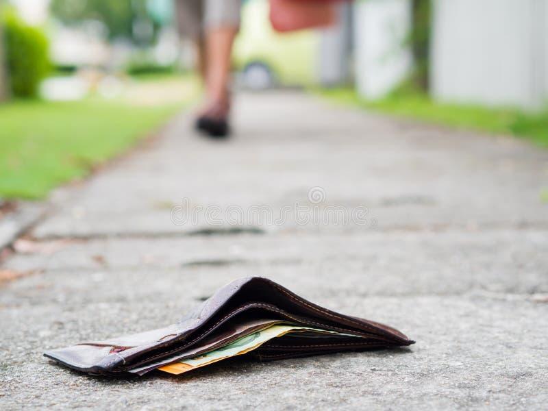 Πορτοφόλι δέρματος Ost με την πτώση χρημάτων στο πεζοδρόμιο στοκ εικόνες