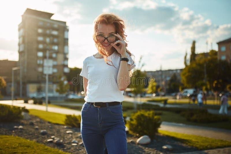 Πορτρέτα ενός γοητευτικού κοκκινομάλλους κοριτσιού με ένα χαριτωμένο πρόσωπο Τοποθέτηση κοριτσιών για τη κάμερα στο κέντρο πόλεων στοκ φωτογραφίες με δικαίωμα ελεύθερης χρήσης