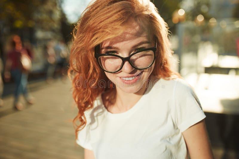 Πορτρέτα ενός γοητευτικού κοκκινομάλλους κοριτσιού με ένα χαριτωμένο πρόσωπο Τοποθέτηση κοριτσιών για τη κάμερα στο κέντρο πόλεων στοκ εικόνες με δικαίωμα ελεύθερης χρήσης