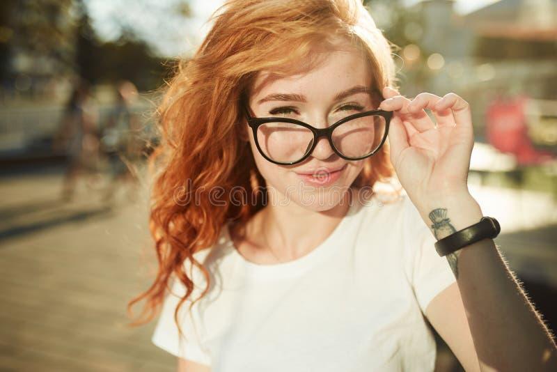 Πορτρέτα ενός γοητευτικού κοκκινομάλλους κοριτσιού με ένα χαριτωμένο πρόσωπο Τοποθέτηση κοριτσιών για τη κάμερα στο κέντρο πόλεων στοκ εικόνα