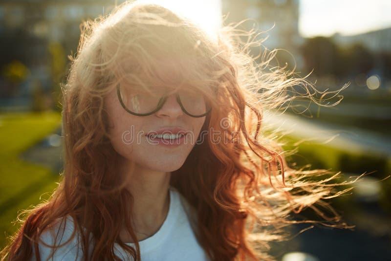 Πορτρέτα ενός γοητευτικού κοκκινομάλλους κοριτσιού με ένα χαριτωμένο πρόσωπο Τοποθέτηση κοριτσιών για τη κάμερα στο κέντρο πόλεων στοκ εικόνες