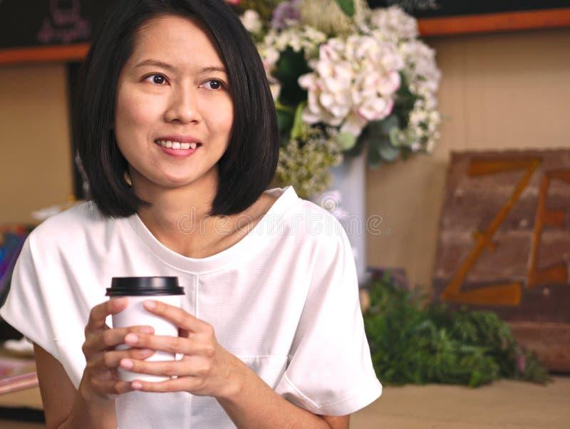 Πορτρέτα της ασιατικής γυναίκας που κρατούν ένα φλιτζάνι του καφέ από δύο χέρια που κοιτάζουν στο αριστερό χέρι της στην άνετη κα στοκ φωτογραφίες