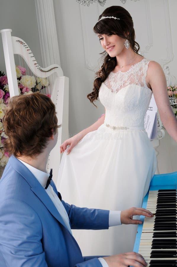Πορτρέτα του όμορφου παιχνιδιού γυναικών και ανδρών στο πιάνο στοκ φωτογραφία