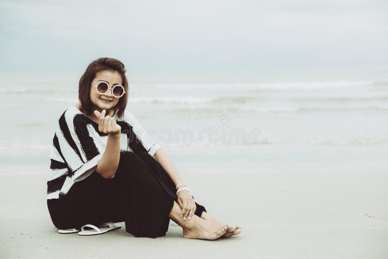 Πορτρέτου ασιατικά ενιαία γυαλιά ηλίου ένδυσης γυναικών hipster indy που εγκαθιστούν στην παραλία στοκ εικόνα