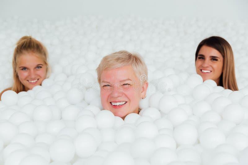 Πορτρέτου ευτυχής στάση μητέρων και κορών φίλων ενήλικη που περιβάλλεται από τις άσπρες πλαστικές σφαίρες στοκ φωτογραφία