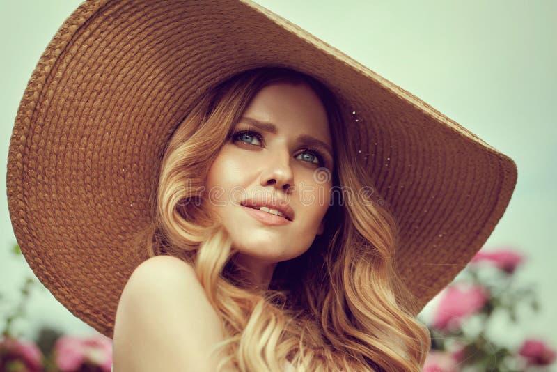 Πορτρέτου ευτυχής τοποθέτηση γυναικών χαμόγελου όμορφη νέα κοντά στα λουλούδια στοκ φωτογραφία με δικαίωμα ελεύθερης χρήσης