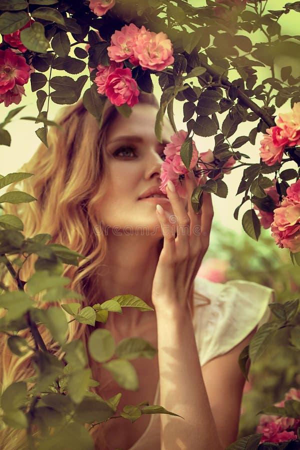 Πορτρέτου ευτυχής τοποθέτηση γυναικών χαμόγελου όμορφη νέα κοντά στα λουλούδια στοκ φωτογραφίες