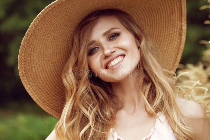 Πορτρέτου ευτυχής τοποθέτηση γυναικών χαμόγελου όμορφη νέα κοντά στα λουλούδια σε έναν κήπο στοκ εικόνα με δικαίωμα ελεύθερης χρήσης