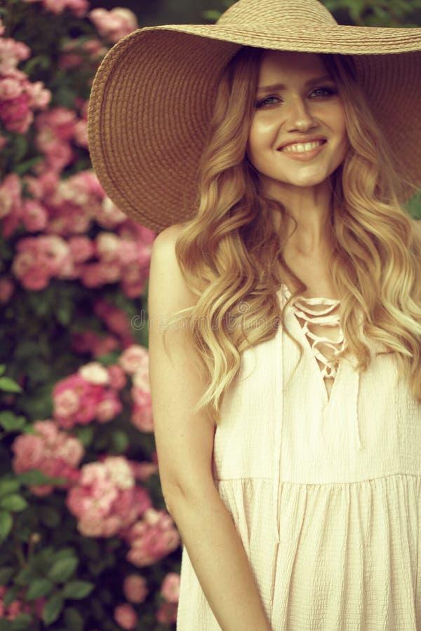Πορτρέτου ευτυχής τοποθέτηση γυναικών χαμόγελου όμορφη νέα κοντά στα λουλούδια σε έναν κήπο στοκ φωτογραφία με δικαίωμα ελεύθερης χρήσης