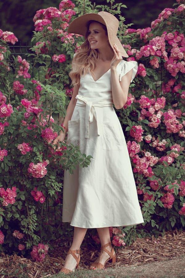 Πορτρέτου ευτυχής τοποθέτηση γυναικών χαμόγελου όμορφη νέα κοντά στα λουλούδια στοκ φωτογραφίες με δικαίωμα ελεύθερης χρήσης