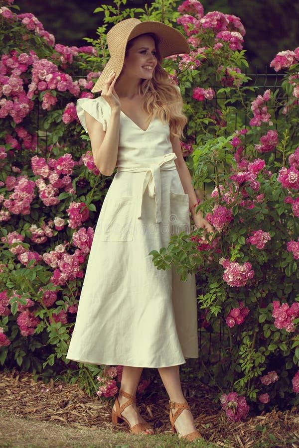 Πορτρέτου ευτυχής τοποθέτηση γυναικών χαμόγελου όμορφη νέα κοντά στα λουλούδια σε έναν κήπο στοκ φωτογραφίες