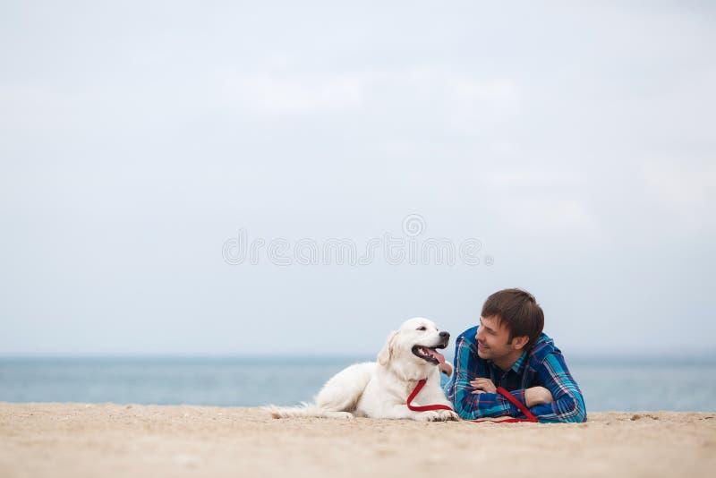 Πορτρέτο άνοιξη ενός νεαρού άνδρα με ένα σκυλί στην παραλία στοκ φωτογραφία με δικαίωμα ελεύθερης χρήσης