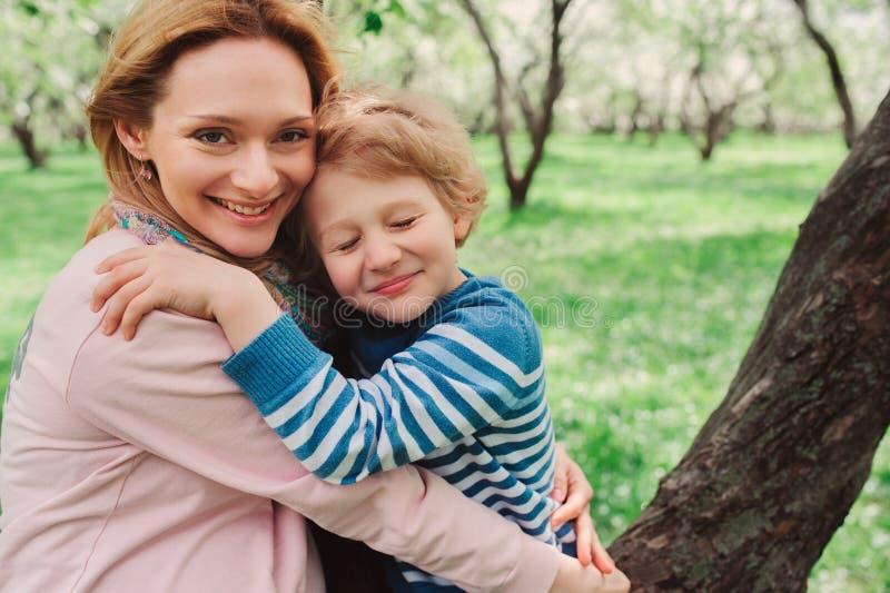 Πορτρέτο άνοιξη της ευτυχούς έγκυου μητέρας που απολαμβάνει τη θερμή ημέρα με το γιο παιδιών στοκ εικόνα