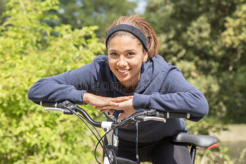Πορτρέτο άσκησης γυναικών χαμόγελου της νέας με το ποδήλατο, υπαίθριο στοκ φωτογραφία