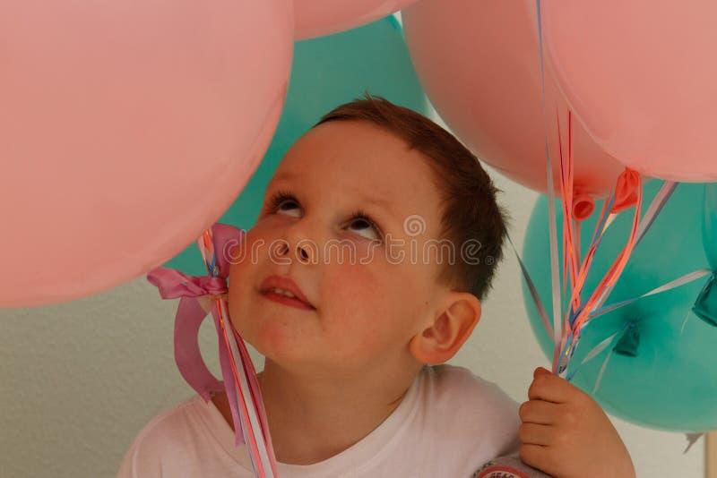 Πορτρέτο, ένα αγόρι με τα ρόδινα και μπλε μπαλόνια, με τις πεταλούδες στοκ εικόνες