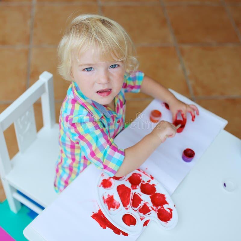 Πορτρέτο λίγου κοριτσιού μικρών παιδιών που χρωματίζει με τη βούρτσα στοκ εικόνες