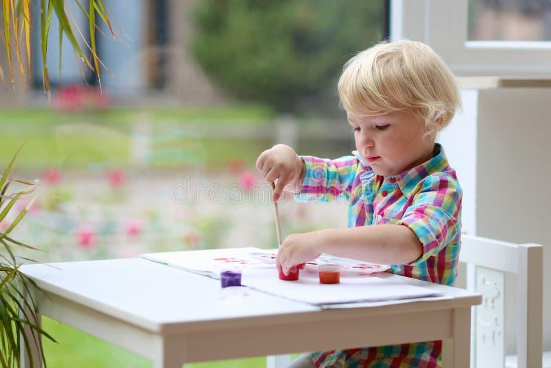 Πορτρέτο λίγου κοριτσιού μικρών παιδιών που χρωματίζει με τη βούρτσα στοκ εικόνα