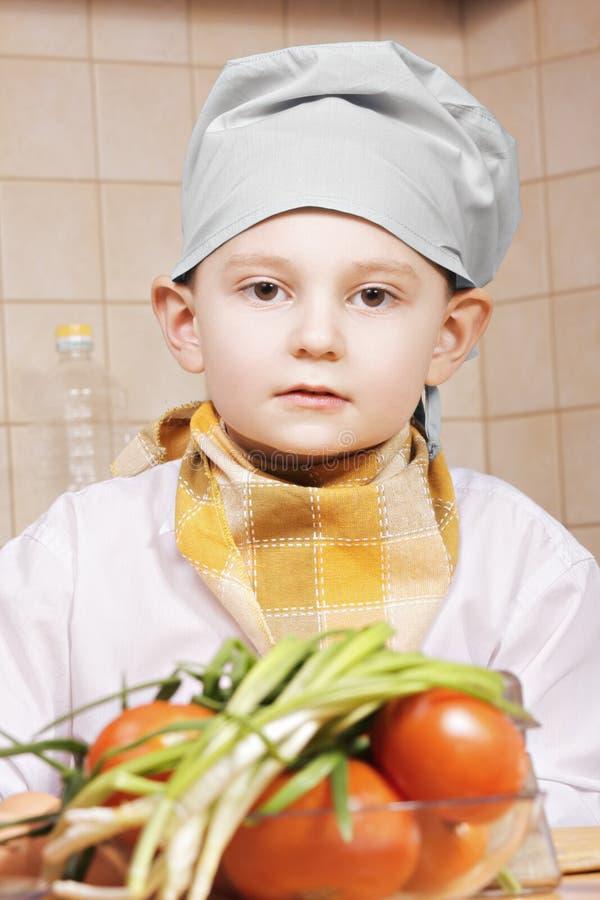 Πορτρέτο λίγου μάγειρα με τις ντομάτες στοκ εικόνες με δικαίωμα ελεύθερης χρήσης