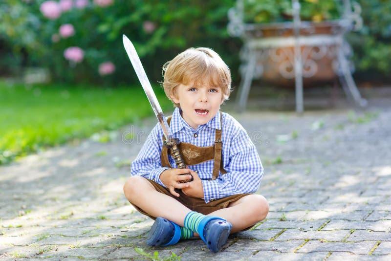 Πορτρέτο λίγου ξανθού αγοριού παιδιών με το ξίφος παιχνιδιών στοκ φωτογραφία με δικαίωμα ελεύθερης χρήσης