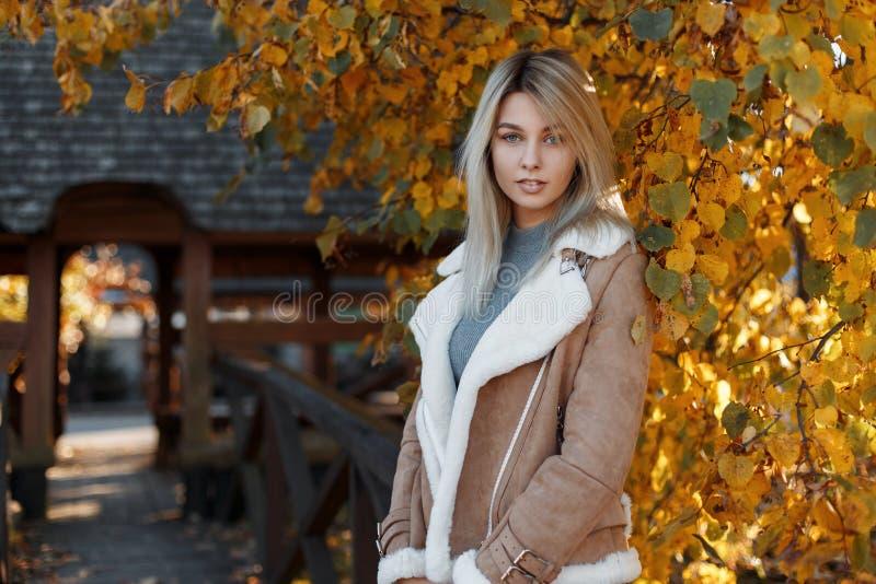 Πορτρέτο αρκετά νέου και όμορφου ενός ξανθού με τα μπλε μάτια Όμορφη νέα γυναίκα που φορά ένα μπεζ μοντέρνο σακάκι με τη γούνα στοκ εικόνα