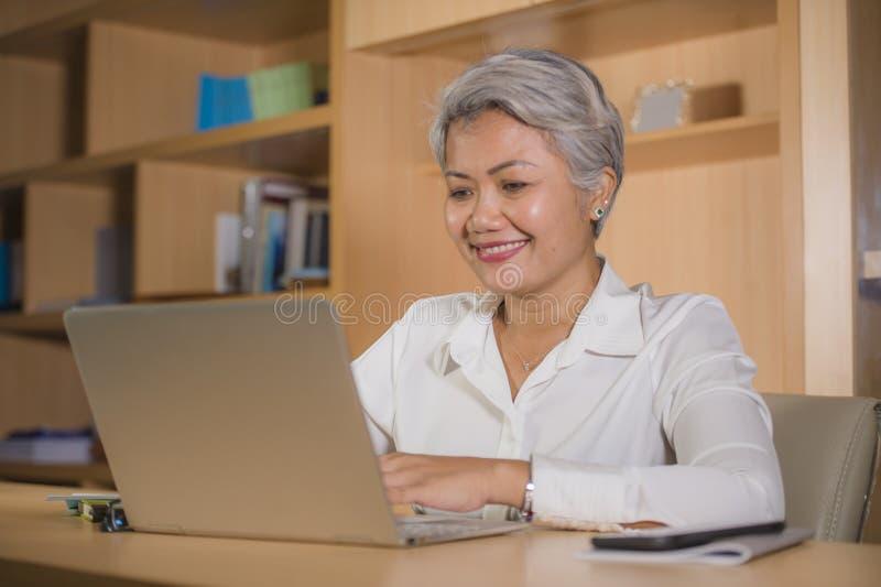 Πορτρέτο γραφείων τρόπου ζωής της ελκυστικής και ευτυχούς επιτυχούς μέσης ηλικίας ασιατικής εργασίας γυναικών στο χαμόγελο γραφεί στοκ εικόνες