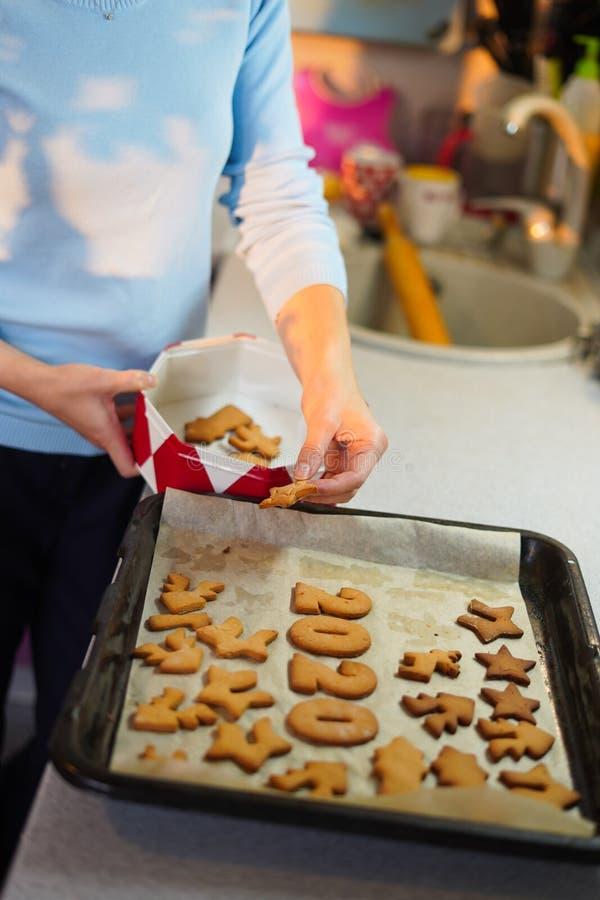 Πορτρέτο γυναικών χεριών που βάζουν μπισκότα σε κουτί με καπάκι στην κουζίνα στοκ εικόνες