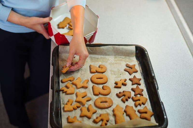 Πορτρέτο γυναικών χεριών που βάζουν μπισκότα σε κουτί με καπάκι στην κουζίνα στοκ φωτογραφία