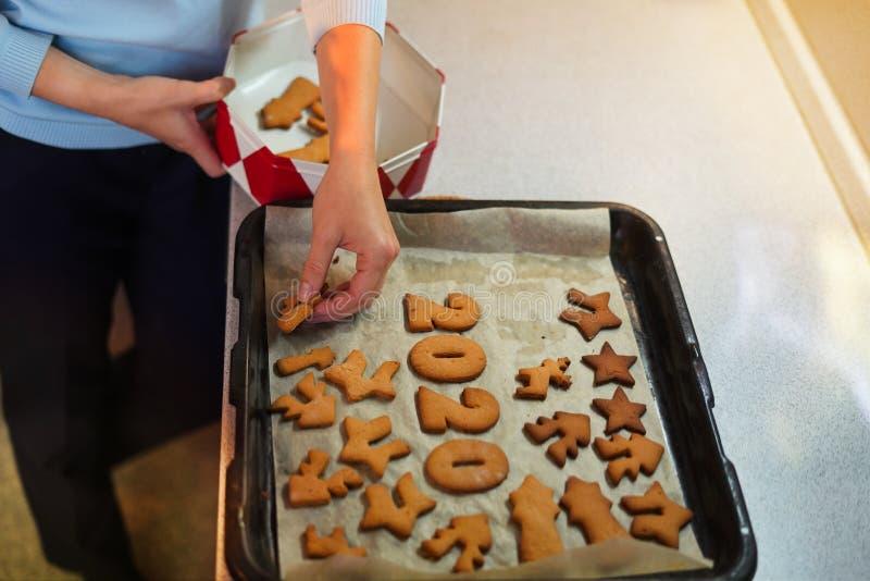 Πορτρέτο γυναικών χεριών που βάζουν μπισκότα σε κουτί με καπάκι στην κουζίνα στοκ φωτογραφίες