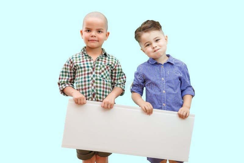 Πορτρέτο δύο αγοριών που κρατούν το άσπρο σημάδι στο απομονωμένο υπόβαθρο στοκ εικόνα