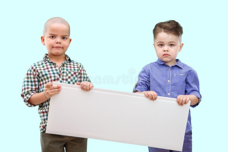 Πορτρέτο δύο αγοριών που κρατούν το άσπρο σημάδι στο απομονωμένο υπόβαθρο στοκ φωτογραφίες