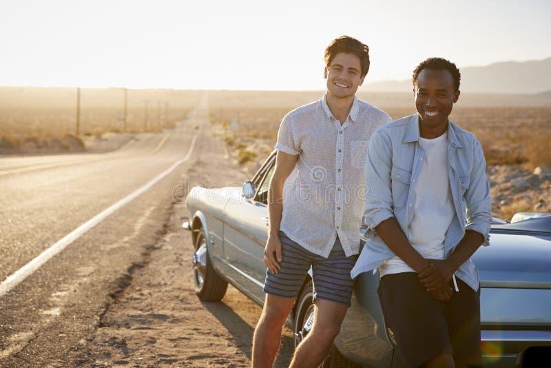 Πορτρέτο δύο αρσενικών φίλων που απολαμβάνουν το οδικό ταξίδι που στέκεται δίπλα στο κλασικό αυτοκίνητο στην εθνική οδό ερήμων στοκ εικόνες