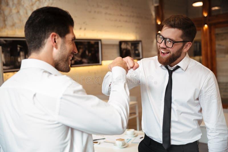 Πορτρέτο δύο εύθυμων επιχειρηματιών που κάνουν την πρόσκρουση πυγμών στοκ φωτογραφία με δικαίωμα ελεύθερης χρήσης