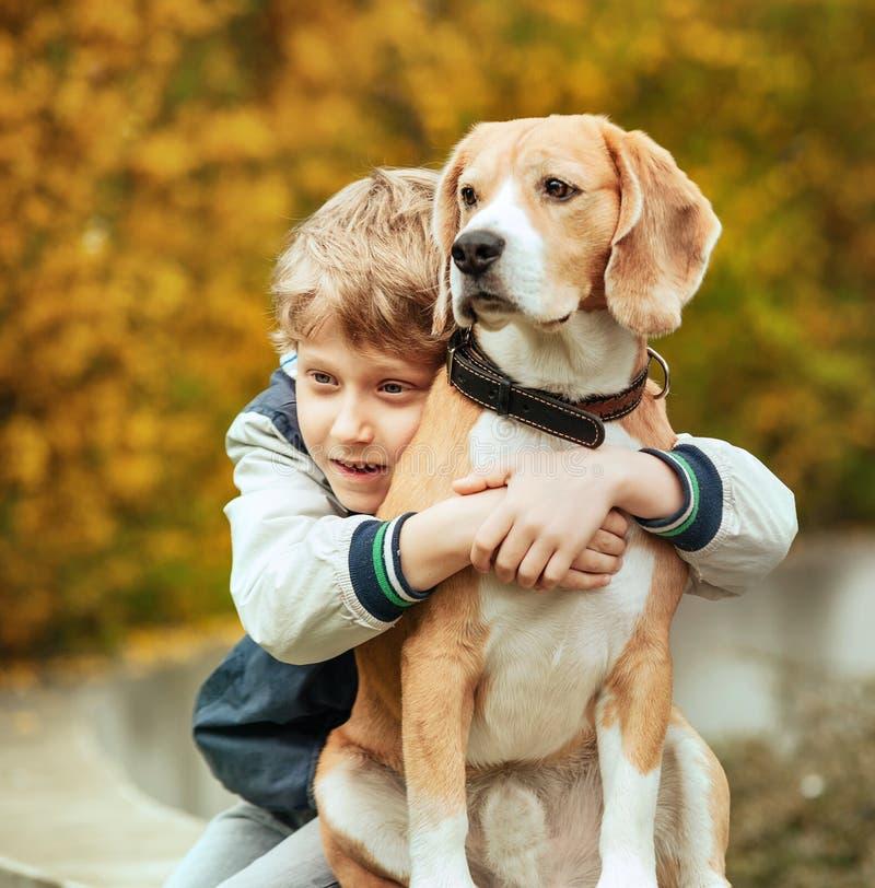 Πορτρέτο δύο καλύτερων φίλων - σκυλί λαγωνικών αγκαλιασμάτων μικρών παιδιών στοκ εικόνες