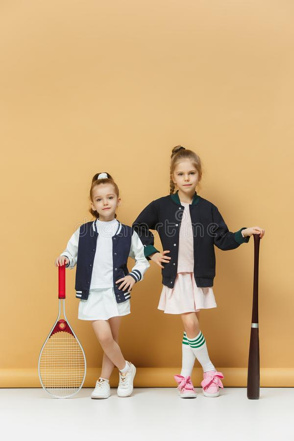 Πορτρέτο δύο κοριτσιών ως τενίστες που κρατούν τη ρακέτα αντισφαίρισης όμορφες νεολαίες γυναικών στούντιο ζευγών χορεύοντας καλυμ στοκ φωτογραφίες