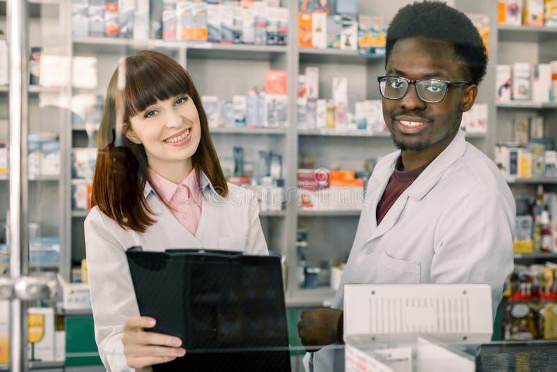 Πορτρέτο δύο χαμογελώντας φιλικών multiethnical φαρμακοποιών που εργάζονται στο σύγχρονο farmacy στοκ φωτογραφία με δικαίωμα ελεύθερης χρήσης