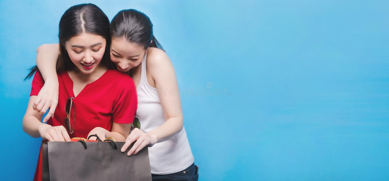 Πορτρέτο δύο όμορφος Ασιάτης που χαμογελούν τις νέες γυναίκες με την έννοια αγορών Τσάντα αγορών εκμετάλλευσης γυναικών με το ελκ στοκ φωτογραφία με δικαίωμα ελεύθερης χρήσης