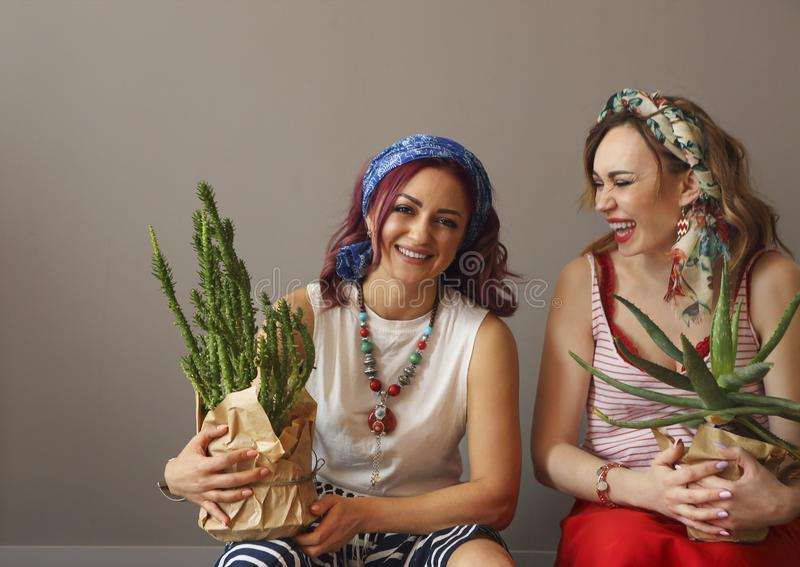 Πορτρέτο δύο όμορφων γυναικών στο φωτεινό ιματισμό και του τόξου στο κεφάλι με τα φωτεινά χείλια που κρατούν τους κάκτους στοκ εικόνες