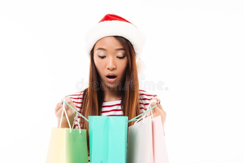 Πορτρέτο ενός έκπληκτου ασιατικού κοριτσιού στο καπέλο Χριστουγέννων στοκ εικόνες