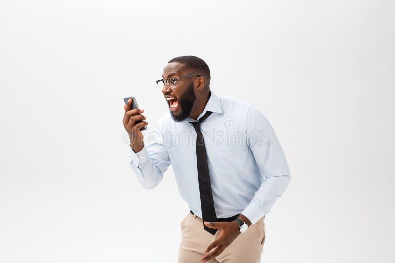Πορτρέτο ενός έκπληκτου επιχειρηματία αφροαμερικάνων που εξετάζει την έξυπνη τηλεφωνική οθόνη του στη δυσπιστία Έννοια ισχυρού στοκ εικόνα με δικαίωμα ελεύθερης χρήσης