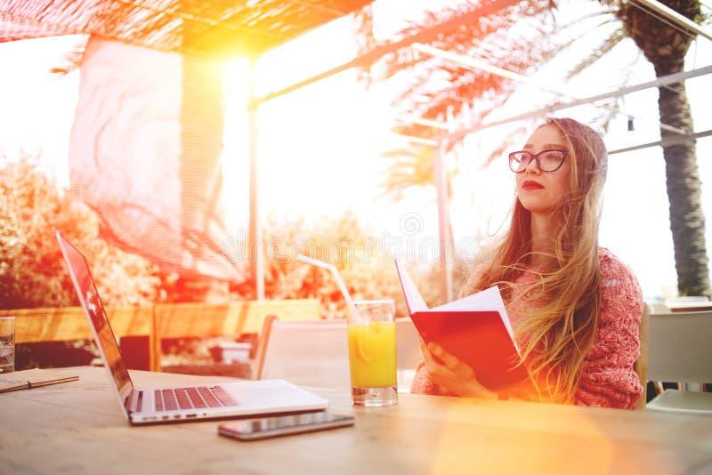 Πορτρέτο ενός έξυπνου βιβλίου ανάγνωσης γυναικών σπουδαστών καθμένος στον μπροστινό ανοικτό φορητό προσωπικό υπολογιστή στο φραγμ στοκ φωτογραφίες με δικαίωμα ελεύθερης χρήσης