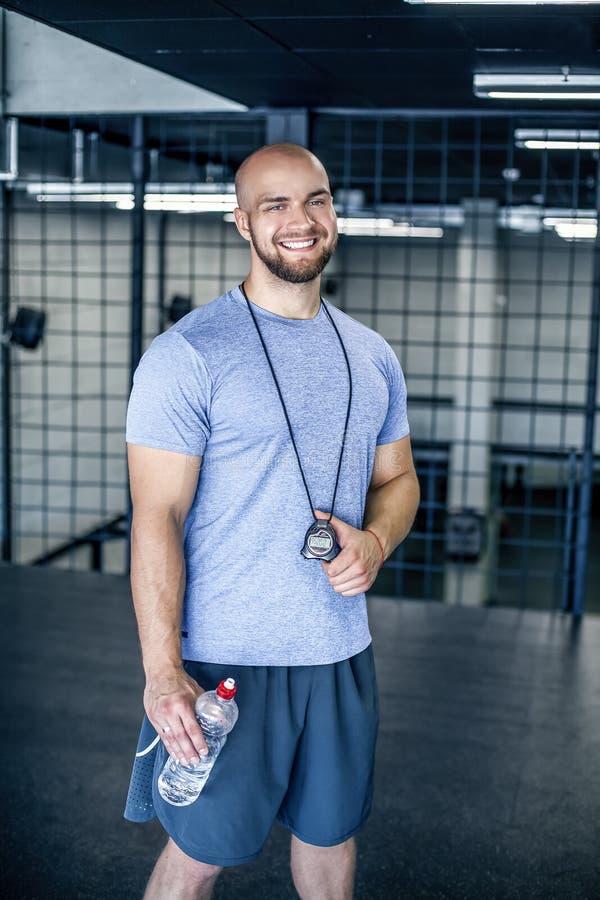 Πορτρέτο ενός αθλητικού προπονητή χαμόγελου με ένα φαλακρό κεφάλι το λ εξετάζει τη κάμερα με το χρονόμετρο με διακόπτη διαθέσιμο  στοκ φωτογραφίες με δικαίωμα ελεύθερης χρήσης